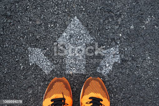 Top view of sport shoes on the road with arrows.