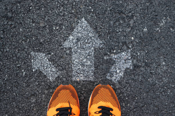 Top view of sport shoes on the road with arrows. Top view of sport shoes on the road with arrows. approaching stock pictures, royalty-free photos & images