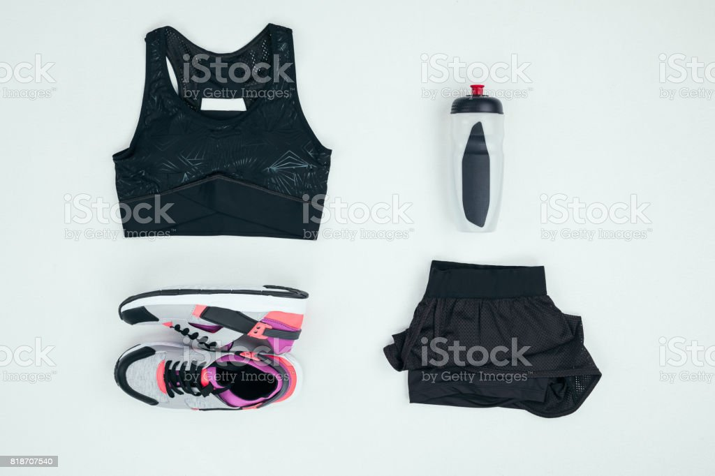top view of sportswear with sneakers and sports bottle isolated on grey stock photo