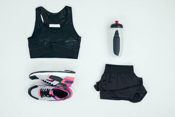 vue de dessus des vêtements de sport avec baskets et sports bouteille isolée sur fond gris - brassière de sport photos et images de collection