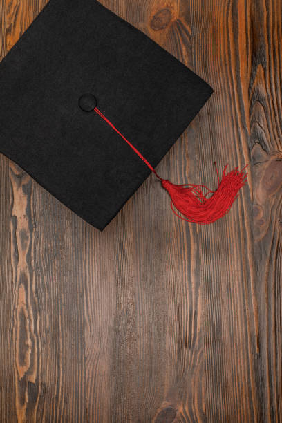 top view of square academic cap on wood background - graduation cap stock pictures, royalty-free photos & images