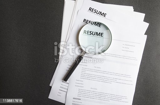 Recruiter`s workplace, pile of resume examples,hand holding magnifier,Concept of analyzing information about new employees