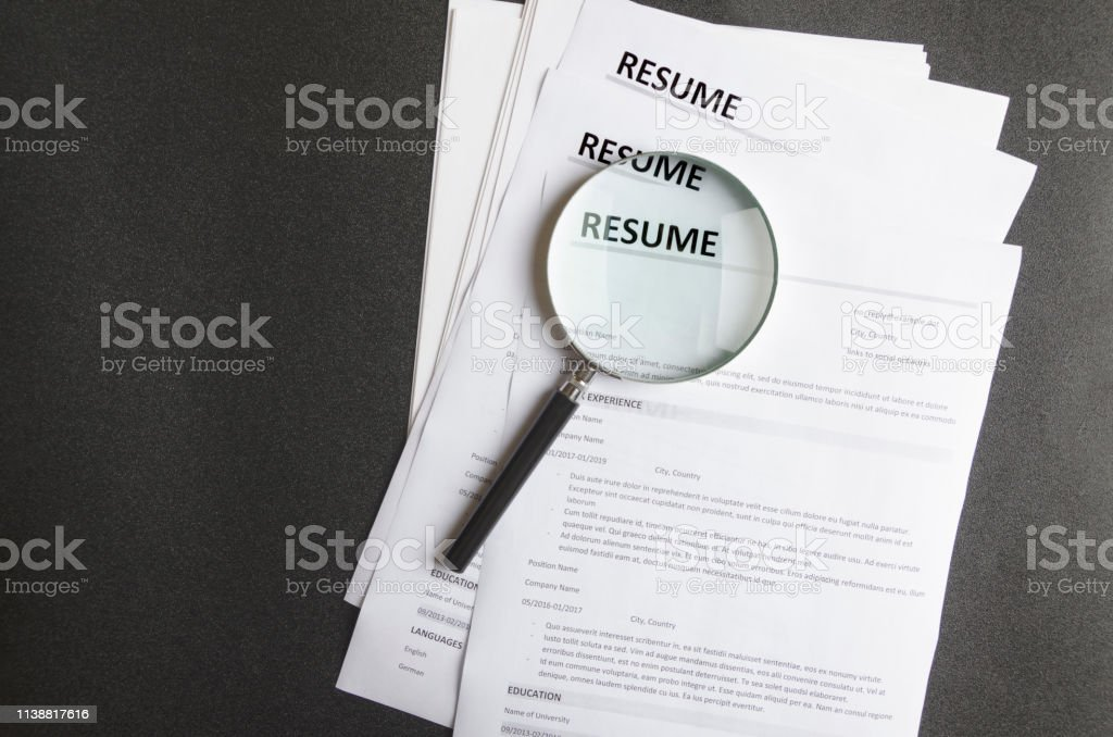 top view of stack of resume filesmagnifier on black