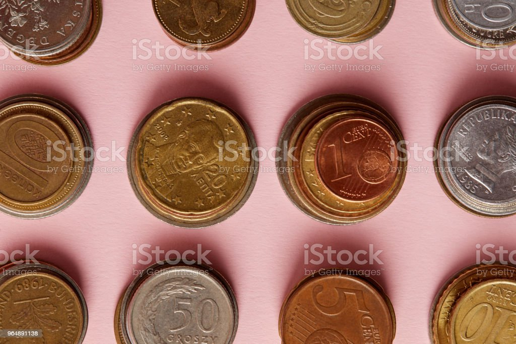 top view of stacks of coins from various countries on pink royalty-free stock photo
