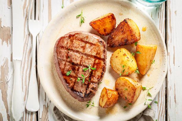 Blick auf Steak und geröstete Kartoffeln mit Wasser – Foto