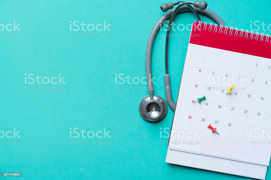 Top view of stethoscope and calendar on the green background, schedule to check up healthy concept stock photo