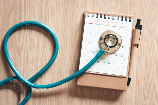 Top view of stethoscope on calendar for health checkup concept., Annual doctor appointment for physical check-up against wooden background., Healthcare Medicine and Insurance concept. stock photo