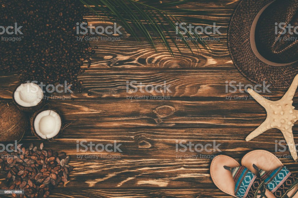 top view of straw hat and flip flops with various tropical travel attributes on wooden surface stock photo