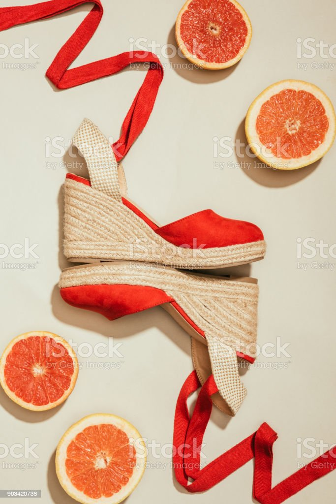 top view of stylish female platform sandals between slices of grapefruits on white background - Zbiór zdjęć royalty-free (Bez ludzi)