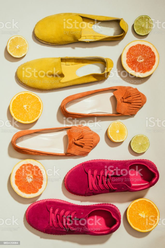 top view of stylish female shoes placed in row surrounded by slices of different citrus fruits on white background - Zbiór zdjęć royalty-free (Bez ludzi)