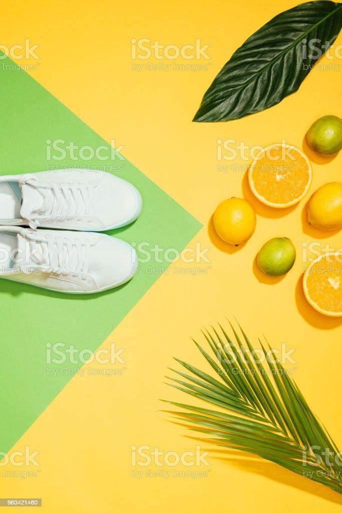 vue de dessus de baskets femmes élégants, tropicales leaves, citrons, limes et tranches d'orange - Photo de A la mode libre de droits