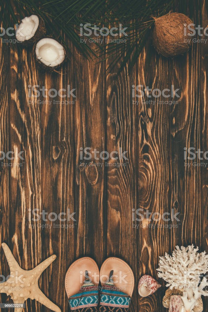 top view of stylish flip flops with various tropical travel attributes on wooden surface stock photo