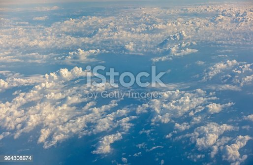621114928istockphoto Top view of sunrise above clouds from airplane window 964308674