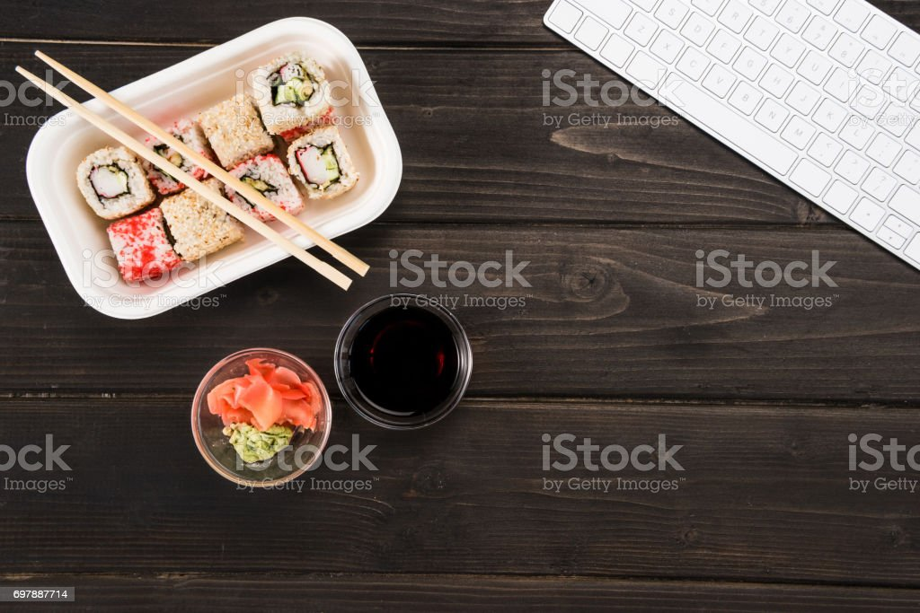Top view of sushi set with computer keyboard on wooden workplace. stock photo