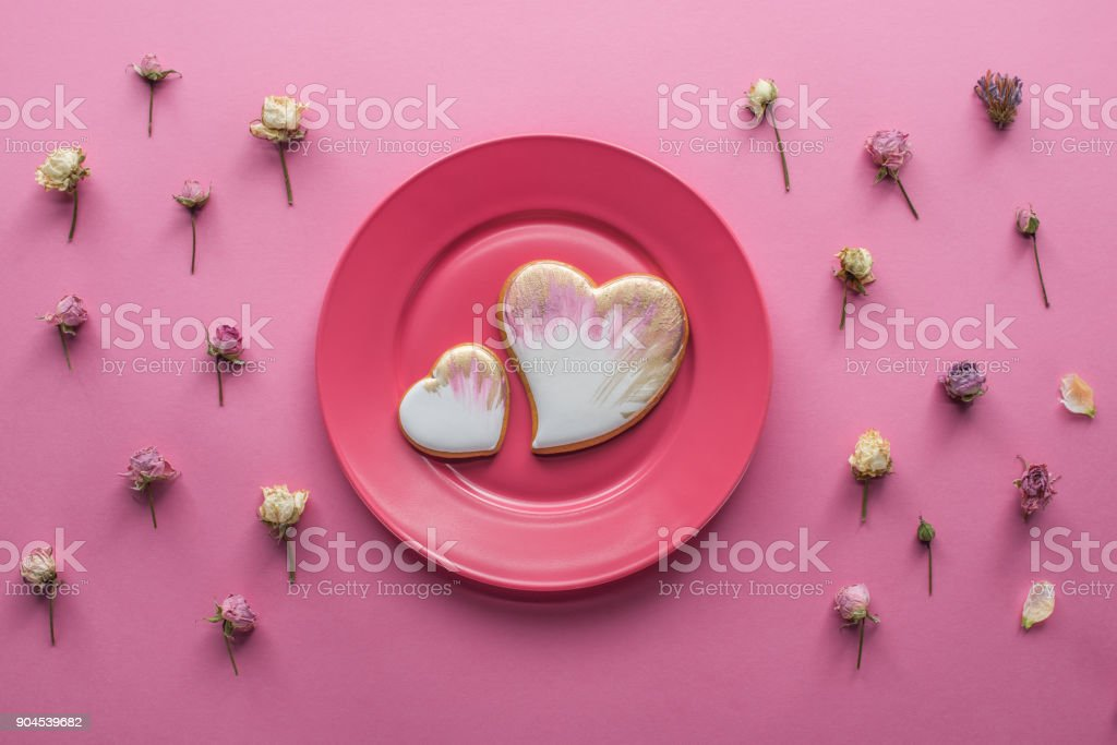 top view of sweet glazed cookies on plate with decorative flowers isolated on pink, st valentines day holiday concept stock photo