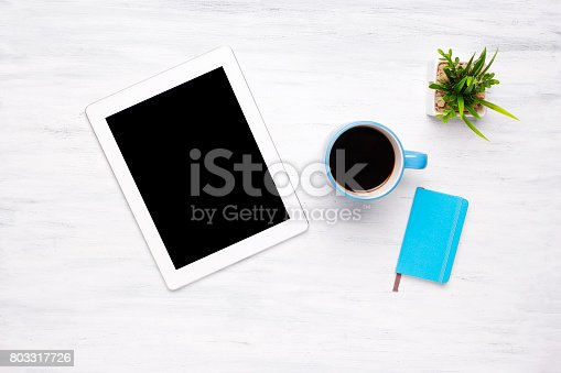 istock Top view of tablet computer and cup of coffee on wooden table 803317726