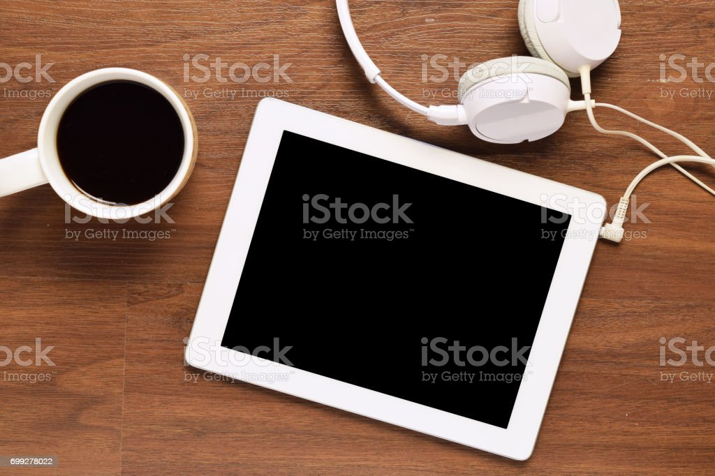 Top view of tablet, headphones and cup of coffee on wooden table stock photo