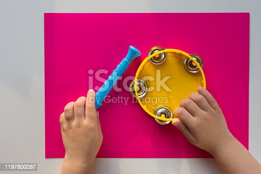 Top view of tambourine and child hands holding pipe on pink background