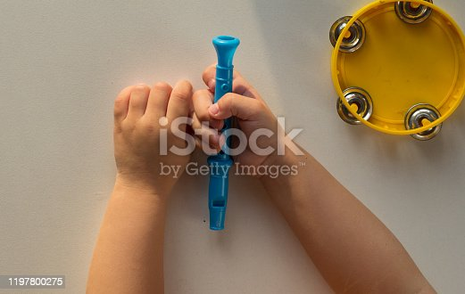 Top view of tambourine and child hands holding pipe on white background