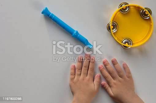 Top view of tambourine, pipe and child hands on white background
