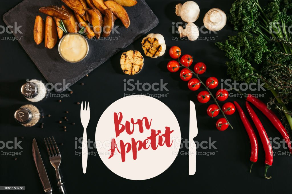 top view of tasty baked potatoes with sauce, spices and vegetables on black with 'bon appetit' lettering stock photo