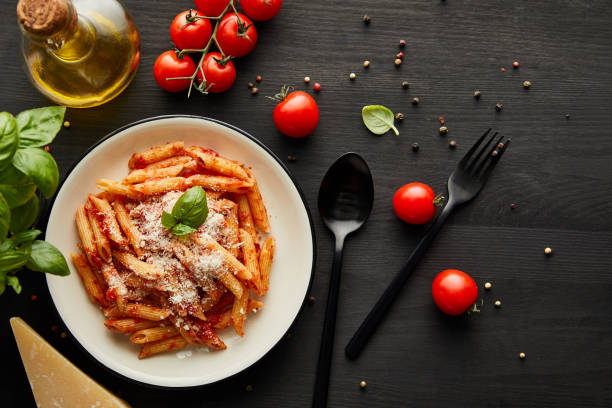top view of tasty bolognese pasta with tomato sauce and Parmesan in white plate near ingredients and cutlery on black wooden background top view of tasty bolognese pasta with tomato sauce and Parmesan in white plate near ingredients and cutlery on black wooden background penne stock pictures, royalty-free photos & images