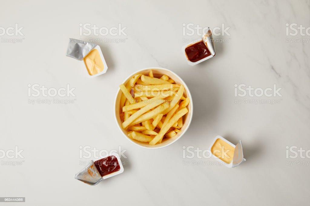 vue de dessus de savoureuses frites français dans une cuvette entourée de conteneurs de sauces sur blanc - Photo de Aliment libre de droits