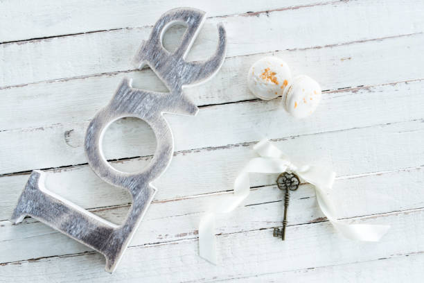Top view of tasty macarons, vintage key with bow and love symbol on wooden tabletop stock photo