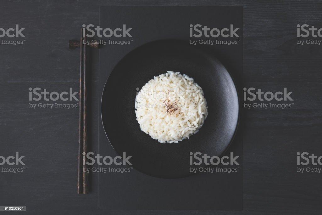 vista superior do arroz saboroso e pauzinhos na tabela preta - foto de acervo