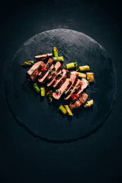top view of tasty sliced grilled meat with asparagus on black slate board stock photo