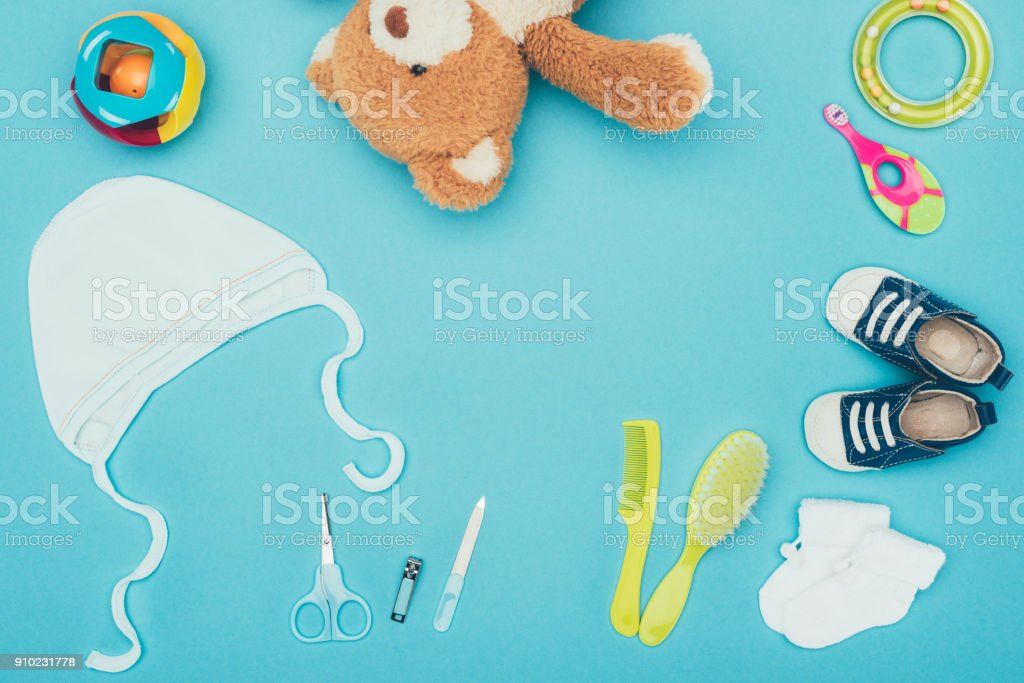 top view of teddy bear and baby clothes with equipment isolated on blue stock photo