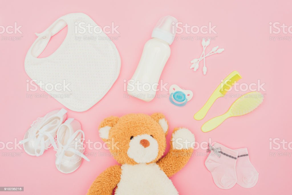 top view of teddy bear and baby equipment isolated on pink stock photo