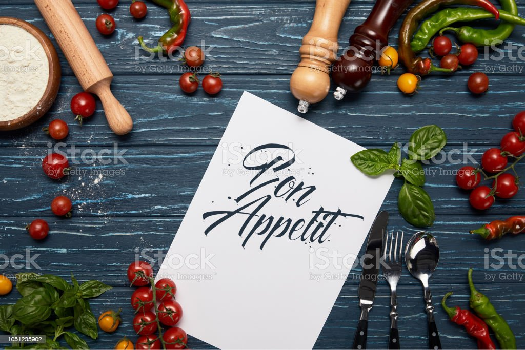 top view of template with 'bon appetit' lettering, fresh vegetables, cutlery and spices on wooden surface stock photo