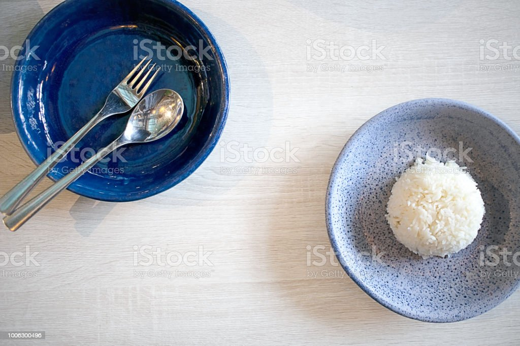 Top view of Thai jasmine rice dish, spoon and fork on white wooden table for copy space stock photo
