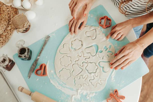 blick auf den teig und die hände, die kekse machen - kinderteil stock-fotos und bilder