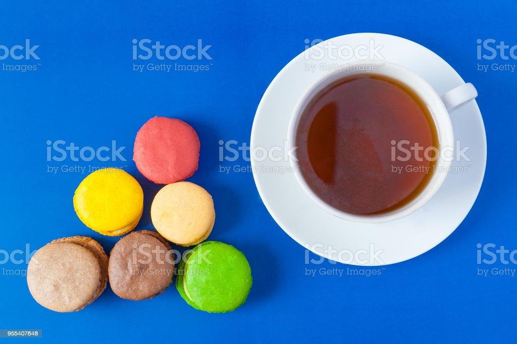 Top view of the french multicolored cakes macarons and a cup of tea on a saucer on a blue background - Zbiór zdjęć royalty-free (Bez ludzi)