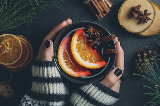 Top view of the girl's hands in a winter sweater are holding a big black cup with hot mulled wine. The concept of cozy winter Holidays.