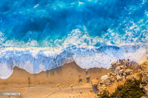 811600544 istock photo Top view of the golden beach and fluorescent blue sea of Milos Beach on the island of Lefkada, Greece 1256296278