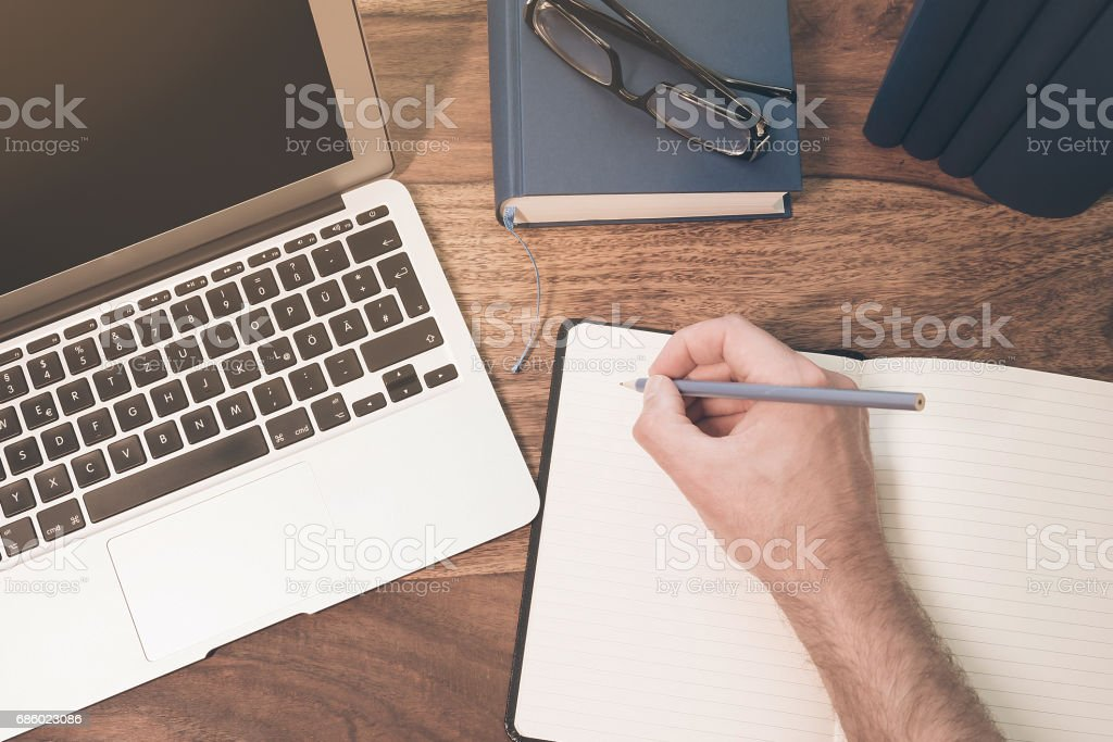 top view of the hand of a male person taking notes on a notepad beneath a notebook computer on a wooden desktop – Foto