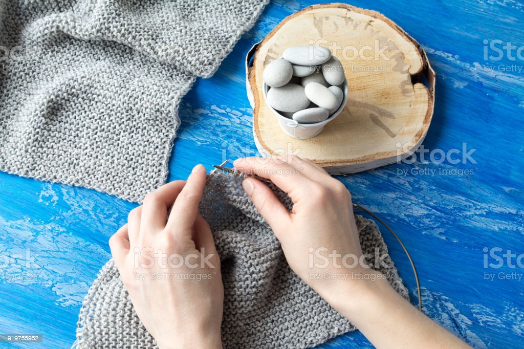 Top view of the  hands of woman knitting a light gray swatch stock photo