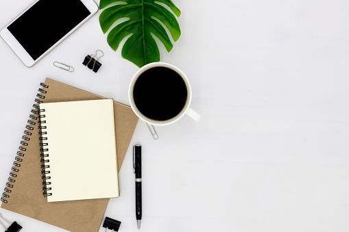 Office supplies or education business concept: Top view view of an open notebook with blank pages and coffee mugs and green leaves on a white background.
