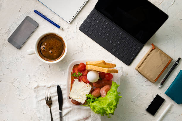 top view of the office work place with computer or laptop pen and phone, nutritious lunch during the works stock photo