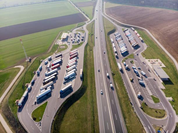 Top-Ansicht des Parkplatzes von Lastwagen, Tankstelle und die Route, auf der Autos rasen. – Foto