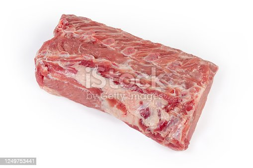 Big piece of the fresh uncooked pork loin with small parts of the ribs on a white background, top view from the ribs