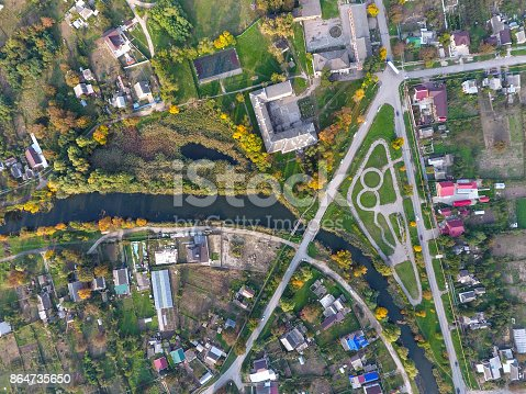 istock Top view of the village. One can see the roofs of the houses and gardens. Road and water in the village. Village bird's-eye view 864735650