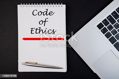 531925785 istock photo Top view of the word Code of Ethics concept written in a notebook with pen and laptop. 1206378765
