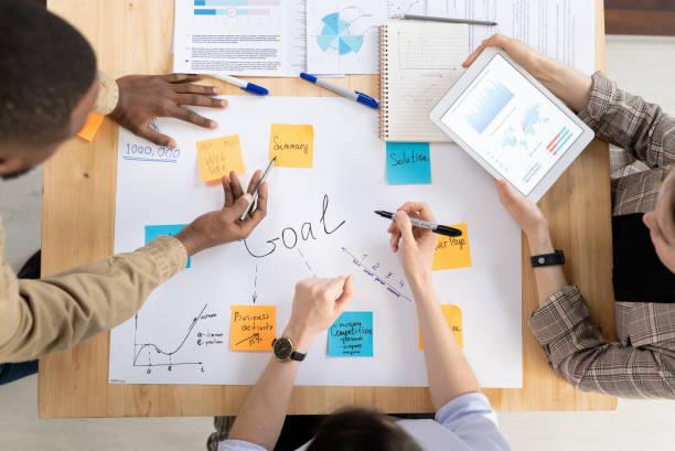top view van drie interculturele managers of analisten bespreken bedrijfsdoelstellingen - medewerkerbetrokkenheid stockfoto's en -beelden