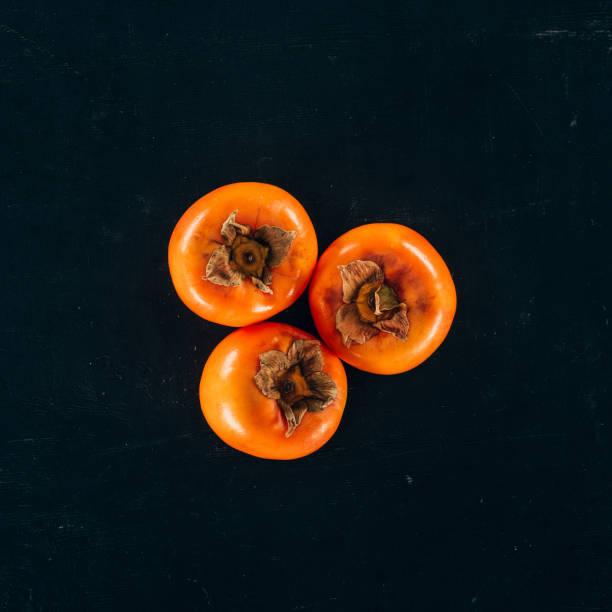 黒に分離された 3 つの柿のトップ ビュー - 熟した ストックフォトと画像