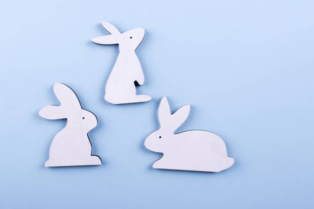 top view  of three white wooden bunny on blue pastel background. copy space - animal markings stock photos and pictures