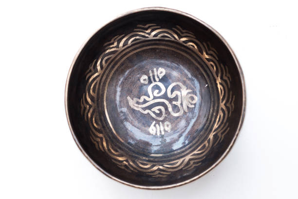 Top view of tibetan buddhist singing bowl close up. Black metal with golden mantras. White background. Religious object. stock photo